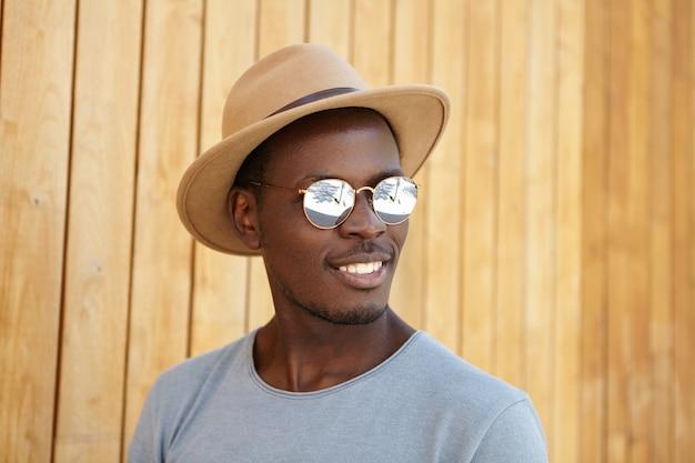 Stilvoller junger mann, der hut und sonnenbrille trägt