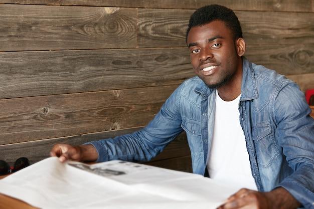 Stilvoller junger mann, der im café sitzt
