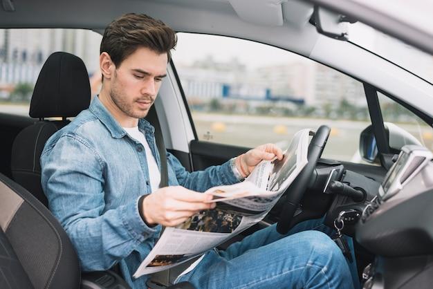Stilvoller junger mann, der in der luxusauto-lesezeitung sitzt