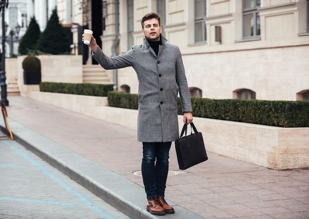 Stilvoller junger mann, der mitnehmerkaffee in der papierschale und anziehendes fahrerhaus auf leerer straße hält