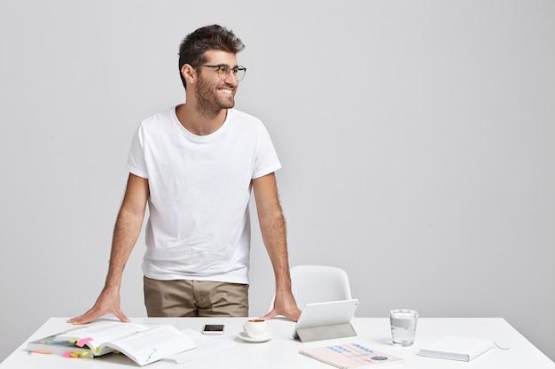 Stilvoller junger mann, der nahe schreibtisch steht