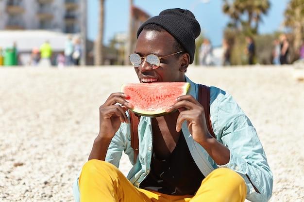 Stilvoller junger mann, der sich am sommertag erfrischt