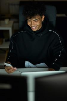 Stilvoller junger mann der technologie mit durchdringendem lächeln, während er das smartphone benutzt, das am tisch sitzt und