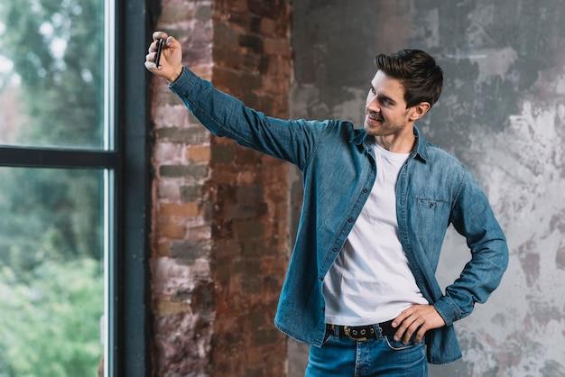 Stilvoller junger mann, der vor dem fenster aufwirft selfie vom mobiltelefon aufwirft