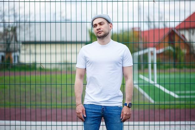 Stilvoller junger mann, ein mann in einem weißen, leeren t-shirt und einem grauen hut, der vor dem hintergrund eines fußballfeldes steht. urbaner kleidungsstil, modernes modisches bild. männermode