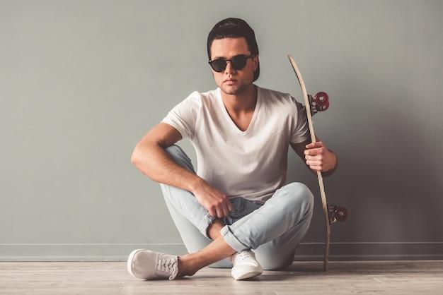 Stilvoller junger mann in der kappe und in den sonnenbrillen.