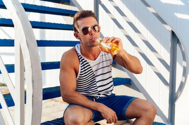 Stilvoller junger mann in der sonnenbrille ein kaltes bier beim sitzen auf treppe am sonnigen tag trinkend