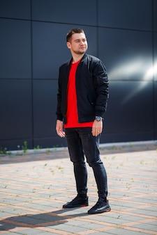 Stilvoller junger mann in einem modischen t-shirt mit sonnenbrille in vintage blue jeans posiert an einem sonnigen tag in der nähe des roten gebäudes im freien. moderner typ auf der straße. jugendstil