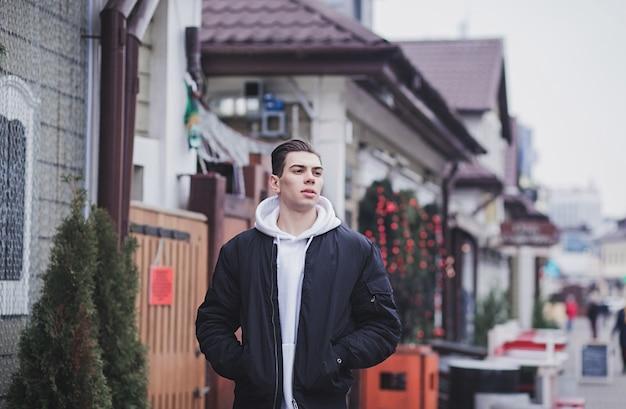 Stilvoller junger mann in einer bomberjacke, die durch die stadt geht
