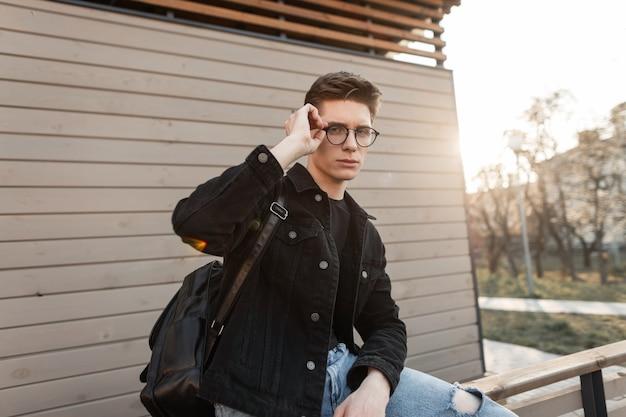 Stilvoller junger mann in modischer jeanskleidung glättet vintage-brille auf hellem sonnenuntergang