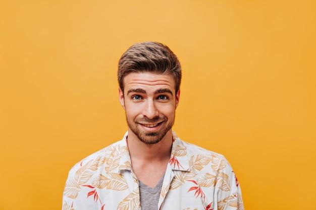 Stilvoller junger mann mit bart und blauen augen in weiß bedruckter sommerkleidung, der auf isolierte orangefarbene wand in die kamera schaut