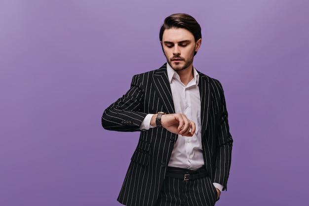 Stilvoller junger mann mit brünetten haaren, weißem hemd und klassischem gestreiftem anzug, der die uhr auf seiner hand isoliert über der violetten wand betrachtet