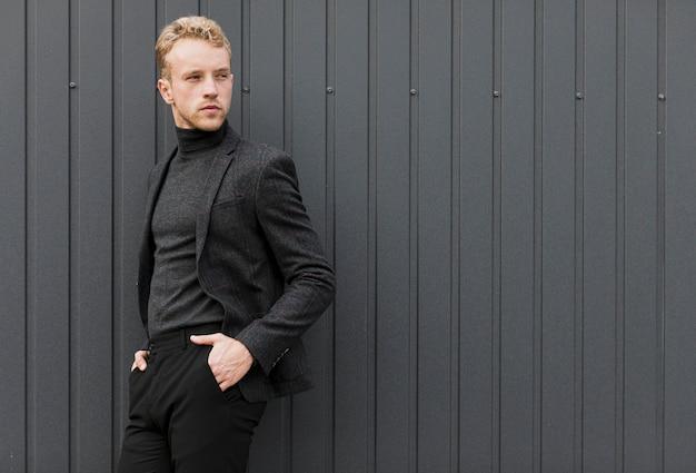 Stilvoller junger mann mit den händen in den taschen