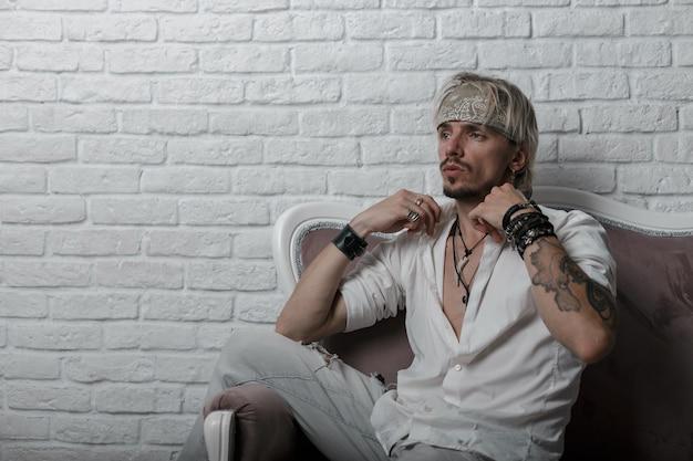 Stilvoller junger mann mit einem kopftuch mit einem bart mit einem tattoo in modischer sommerkleidung sitzt auf einem weichen vintage-sofa in der nähe einer weißen backsteinmauer im studio.
