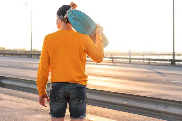 Stilvoller junger mann mit einem longboard auf einer brücke bei sonnenuntergang