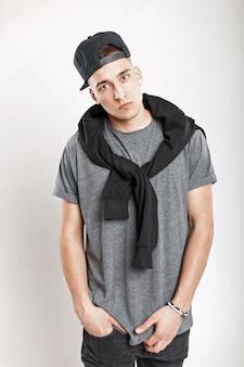 Stilvoller junger mann mit einer baseballkappe in einem grauen t-shirt, das im studio aufwirft.