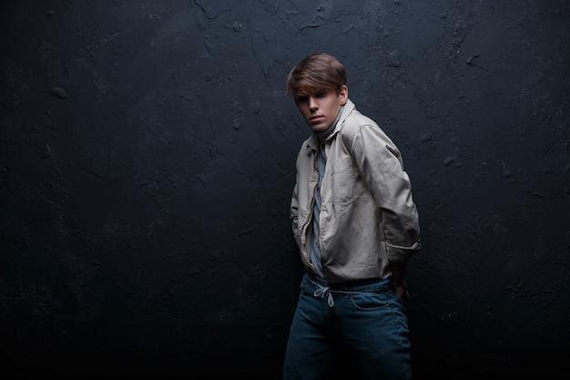 Stilvoller junger mann mit einer modischen frisur in einer weißen coolen stilvollen jacke in stilvollen vintage-jeans in grauem golf steht in einem dunklen studio nahe einer grauen wand. modischer schöner model-typ