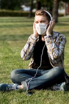 Stilvoller junger mann mit gesichtsmaske, die musik hört