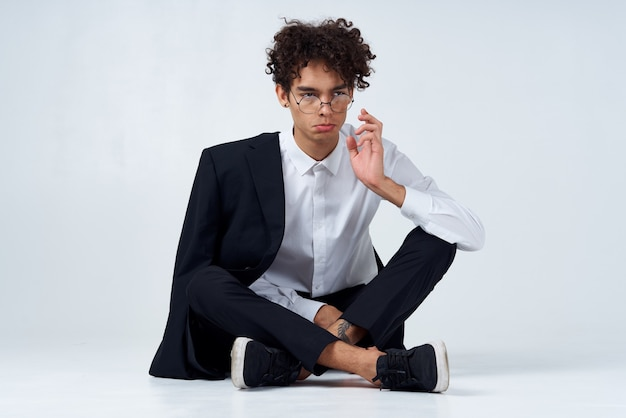 Stilvoller junger mann mit lockigem haar und in einem klassischen anzug auf einem licht drinnen