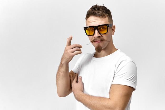 Stilvoller junger mann mit sonnenbrille und weißem t-shirt, das ein auge versteckt