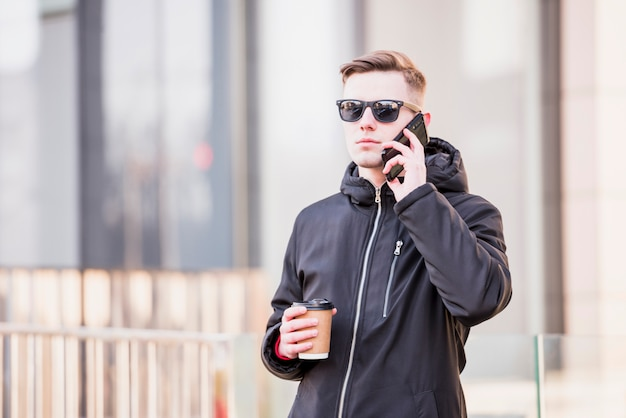 Stilvoller junger mann mit sonnenbrille unter verwendung des handys, der mitnehmerkaffeetasse hält