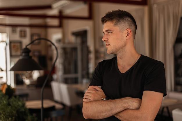 Stilvoller junger mann mit trendiger frisur schaut nach innen weg. attraktiver geschäftsmannmann in einem modischen schwarzen t-shirt, das aufwirft