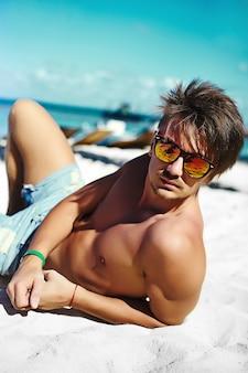 Stilvoller junger sexy hahndsome mit muskeln männlicher vorbildlicher mann, der auf dem strandsand genießt sommerreiseferien nahe ozean in der sonnenbrille liegt