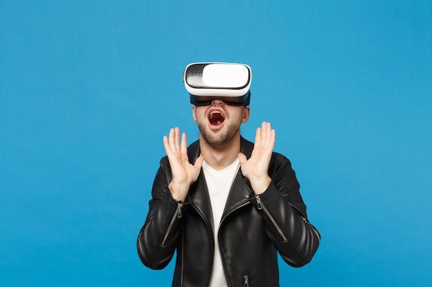 Stilvoller junger unrasierter mann im weißen t-shirt der schwarzen jacke, der im kopfhörer schaut, virtuelle realität vr einzeln auf blauem wandhintergrundstudioporträt. menschen emotionen lifestyle-konzept. kopieren sie platz.