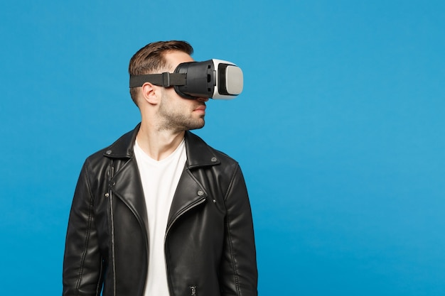 Stilvoller junger unrasierter mann im weißen t-shirt der schwarzen jacke, der im kopfhörer schaut, virtuelle vr-realität einzeln auf blauem wandhintergrundstudioporträt. menschen emotionen lifestyle-konzept. kopieren sie platz.