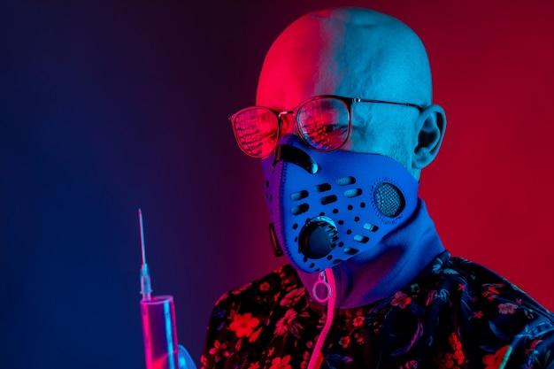 Stilvoller kahler mann, der atemschutzmaske und brille trägt und spritze mit impfstoff hält