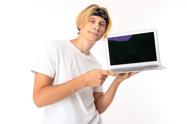 Stilvoller kaukasischer blonder mann zeigt laptop isoliert