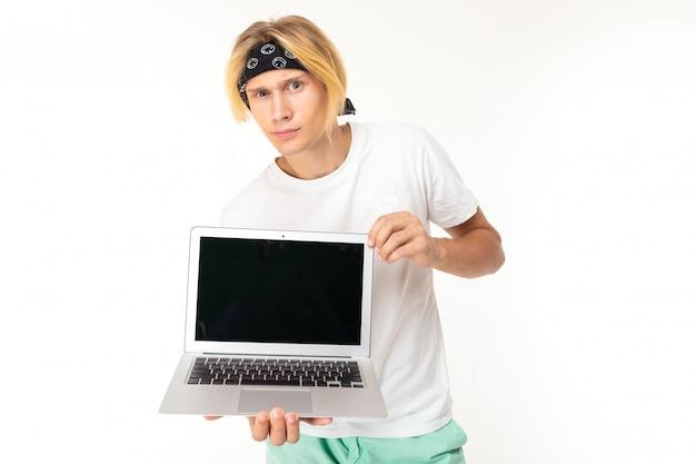 Stilvoller kaukasischer blonder mann zeigt laptop lokalisiert auf weißer wand