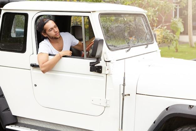 Stilvoller kaukasischer reisender, der pause während der safari-abenteuerreise hat. junger bärtiger hipster-mann im weißen t-shirt sitzt in seinem weißen allrad-suv-auto und schaut aus offenem fenster
