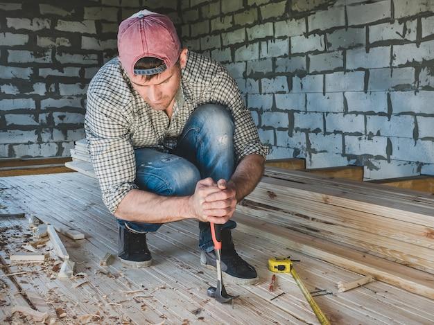 Stilvoller kerl, arbeitend mit werkzeugen auf holz