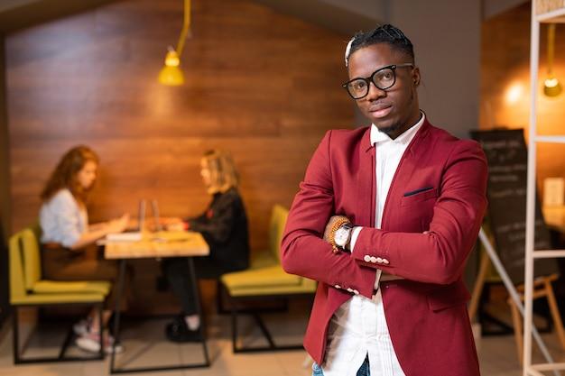 Stilvoller kerl der afrikanischen ethnizität im intelligenten lässigen stehen mit zwei mädchen, die durch tisch vernetzen