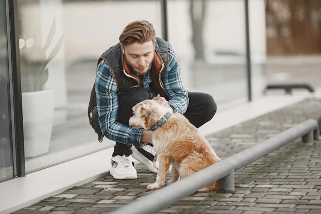 Stilvoller kerl, der mit einem hund spielt. mann in der herbststadt.