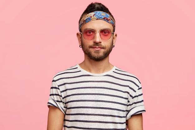Stilvoller kerl, der sonnenbrille und buntes stirnband trägt