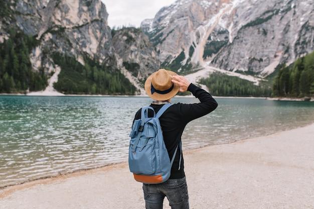 Stilvoller kerl, der weinlesehut trägt, der mit band verziert wird, das am seeufer sich entspannt und wasser betrachtet