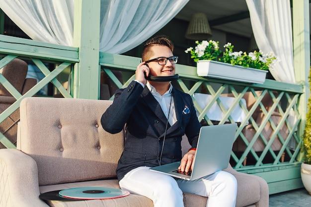 Stilvoller kerl in den gläsern und im gesellschaftsanzug auf sofa mit laptop und kopfhörern