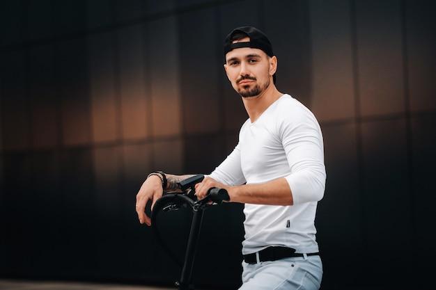 Stilvoller kerl in einem weißen t-shirt und einer kappe auf einem elektroroller in der stadt