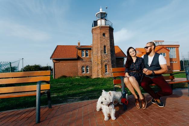 Stilvoller kerl mit seiner freundin sitzen im park zusammen mit zwei weißen hunden