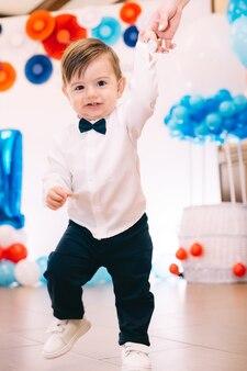 Stilvoller kleiner junge, der in die kamera nahe der fotozone schaut.