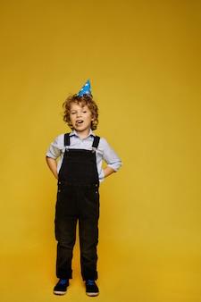 Stilvoller kleiner junge im overall und in der geburtstagskappe, die am gelben hintergrund aufwirft, lokalisiert. kindermode