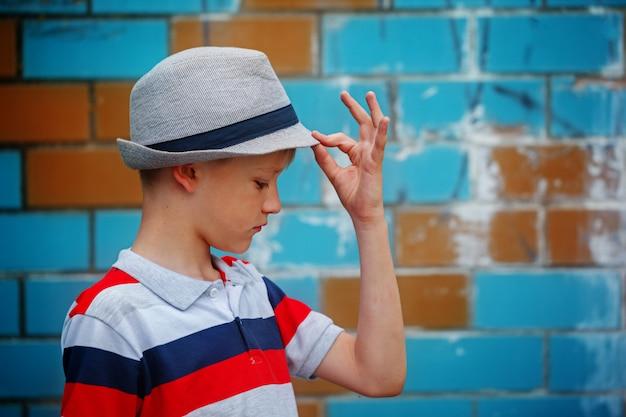 Stilvoller kleiner junge in einem sommerhut steht am sommertag.
