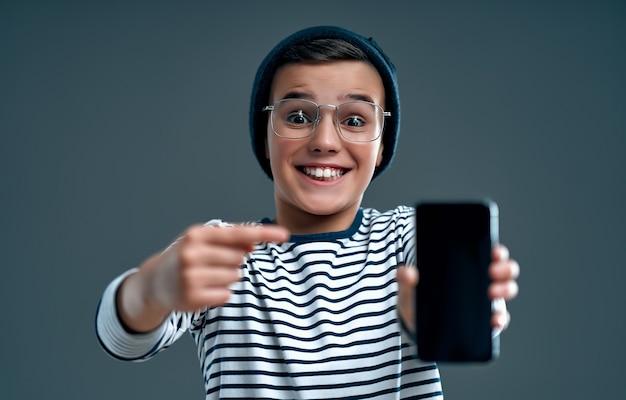 Stilvoller kluger kinderschüler in einem hut und in einer brille zeigt einen finger auf einem smartphone, das auf einem grau isoliert wird.
