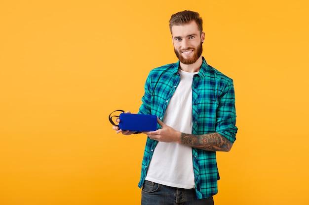 Stilvoller lächelnder junger mann, der drahtlosen lautsprecher glücklich hält, der fröhliche musik der bunten art der musik lokalisiert auf gelber wand hört