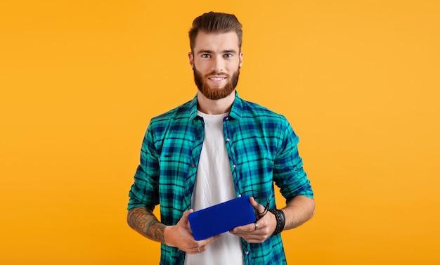 Stilvoller lächelnder junger mann, der drahtlosen lautsprecher hält, der glückliche stimmung der musikbuntart lokalisiert auf gelbem hintergrund hört