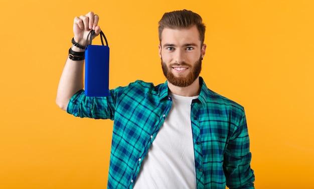 Stilvoller lächelnder junger mann, der drahtlosen lautsprecher hält, der musik auf orange hört