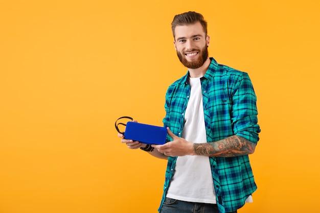 Stilvoller lächelnder junger mann, der einen drahtlosen lautsprecher hält und musik hört