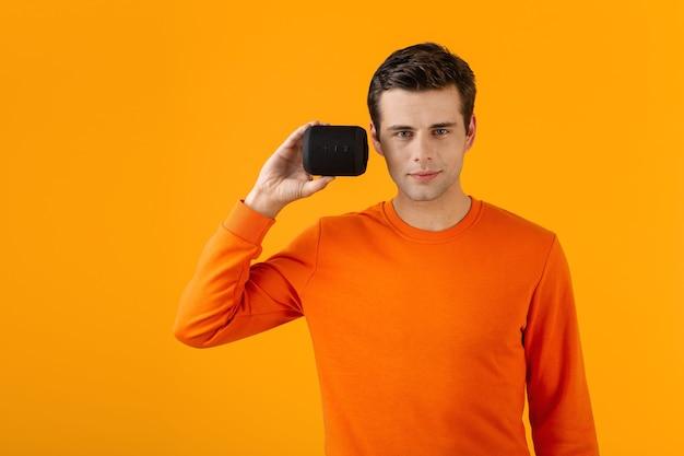 Stilvoller lächelnder junger mann im orangefarbenen pullover, der drahtlosen lautsprecher glücklich hält, musik zu hören